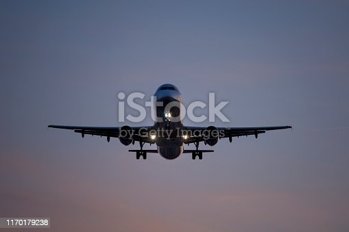 Landing approach of an airplane at dusk - low-angle view