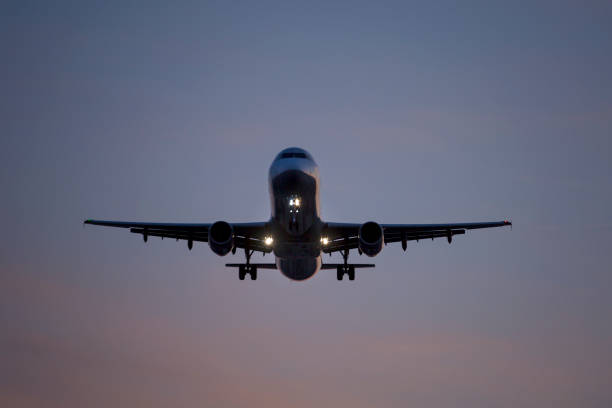 Airplane landing approach at dusk stock photo