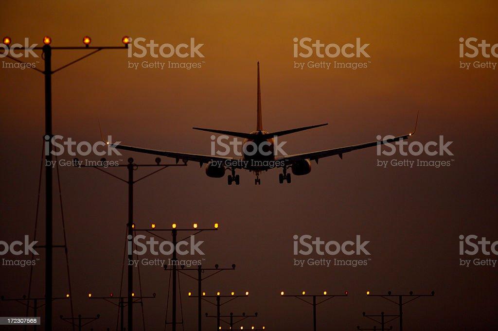 Airplane landing at dusk royalty-free stock photo