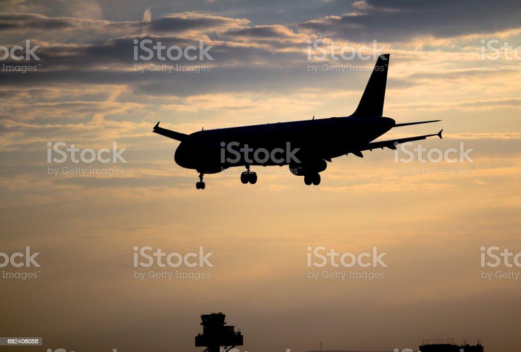 Airplane landing at sunset royalty-free stock photo