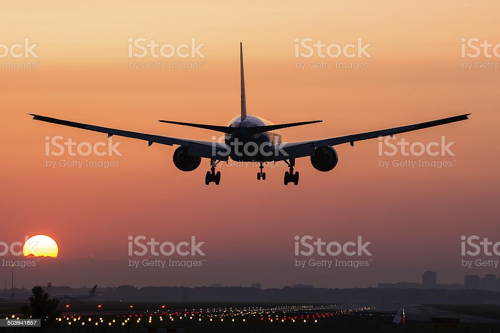Airplane landing during sunrise stock photo