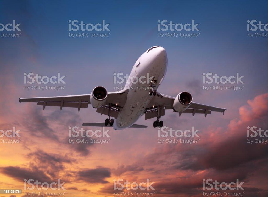 Airplane landing in sunset light stock photo