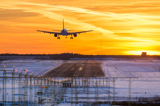 Airplane landing in sunset Airplane landing to airport runway in sunset in winter airfield stock pictures, royalty-free photos & images