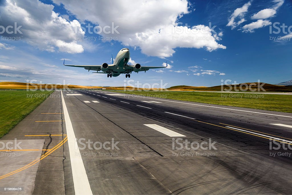 Airplane landing on a sunny day stock photo