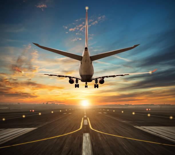 Airplane landing to airport runway in sunset light stock photo