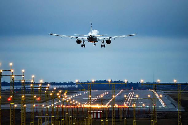 avión aterrizando hasta tarde por la noche a las pistas - aterrizar fotografías e imágenes de stock