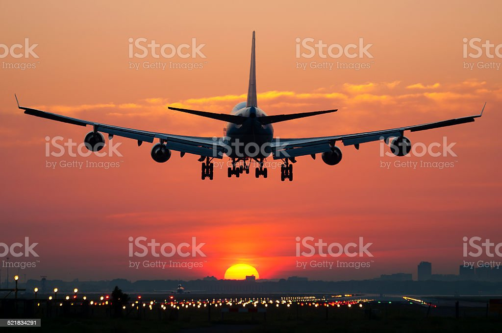 Airplane landing with sunrise stock photo