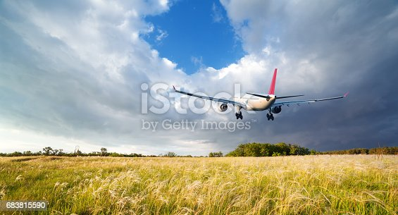 816320512 istock photo Airplane. Landscape with big white passenger airplane is flying in the red sky over the clouds at colorful sunset. Journey. Passenger airliner is landing at dusk. Business trip. Commercial plane 683815590