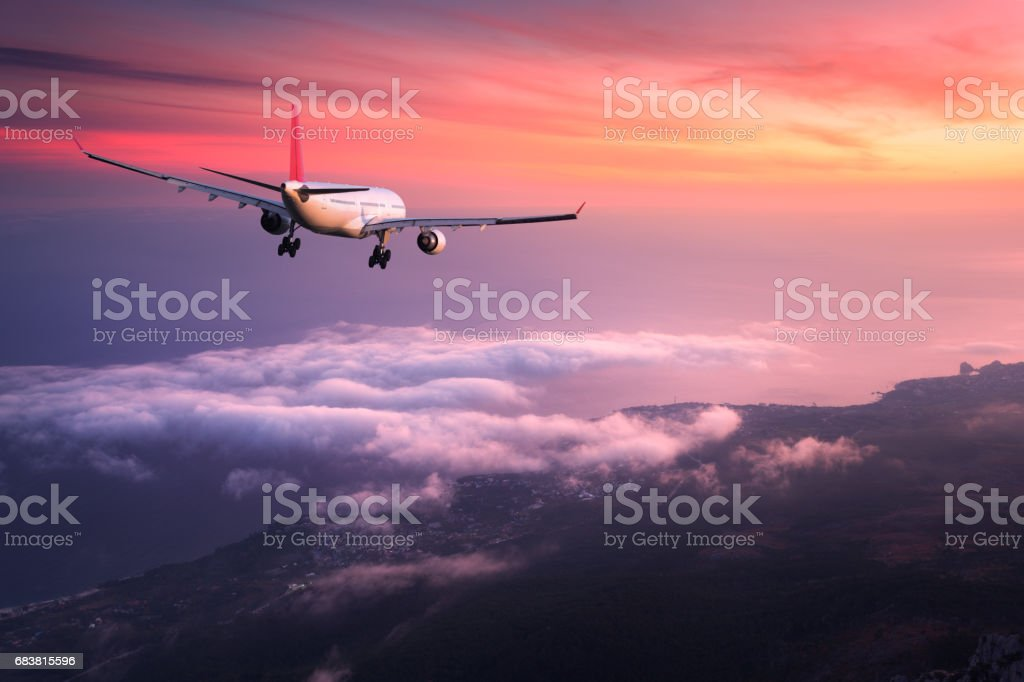Airplane. Landscape with big white passenger airplane is flying in the red sky over the clouds at colorful sunset. Journey. Passenger airliner is landing at dusk. Business trip. Commercial plane - foto stock
