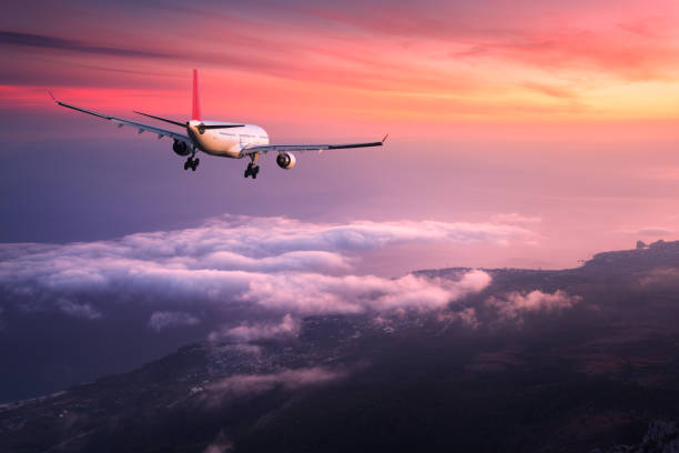 Airplane. Landscape with big white passenger airplane is flying in the red sky over the clouds at colorful sunset. Journey. Passenger airliner is landing at dusk. Business trip. Commercial plane stock photo