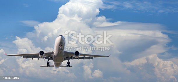 816320512 istock photo Airplane. Landscape with big white passenger airplane is flying in the blue sky over the clouds in sunny day. Journey. Beautiful passenger aircraft is landing. Business trip. Commercial plane 816320486
