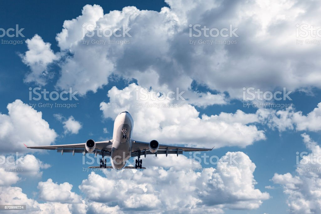 Airplane. Landscape with white passenger airplane is flying in the blue sky with clouds at sunny day. Travel background. Passenger airliner at sunrise. Business trip. Commercial plane. Aircraft. Jet stock photo