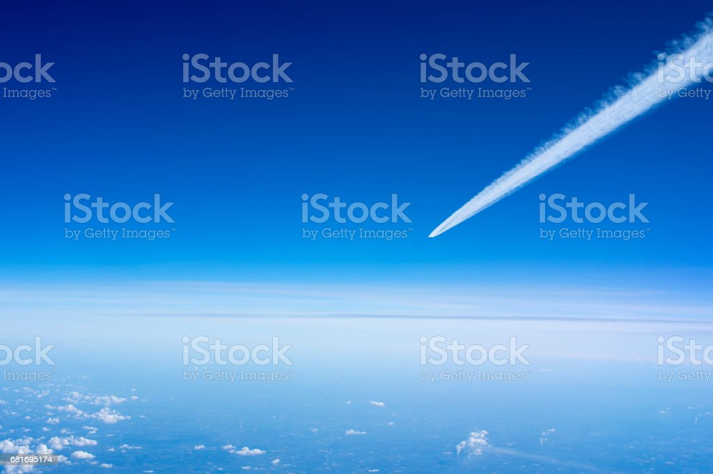 Airplane Leaving Contrail against dark Blue sky stock photo