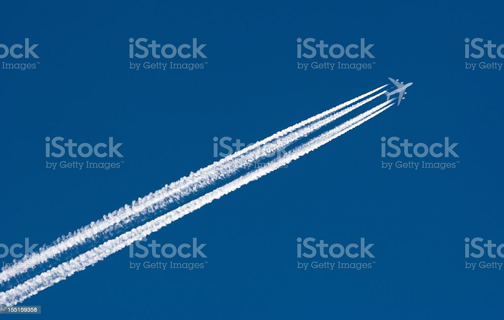 Airplane Leaving Contrail with four lines of smoke behind it stock photo