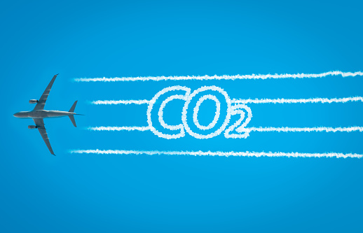 Airplane leaving jet contrails with CO2 word inside. Suitable for ecofriendly and sustainable journey concepts and the negative impact on the environment.