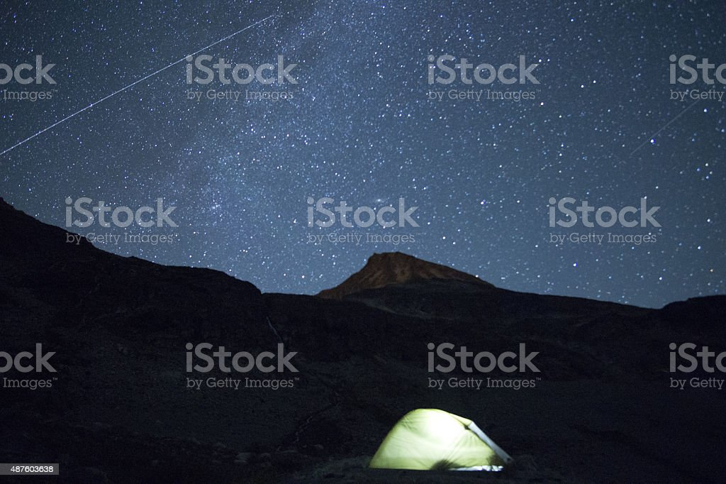 Airplane light trail under starry night sky stock photo