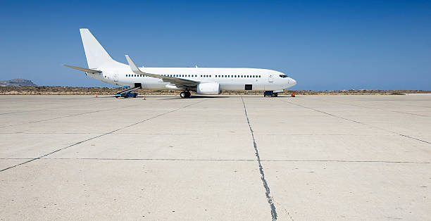 Airplane loading on airport Filling cargo by side profile of an airplane on tarmac. airfield stock pictures, royalty-free photos & images