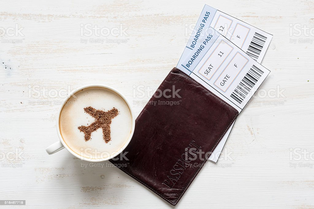 Airplane made of cinnamon in cappuccino and boarding passes. stock photo