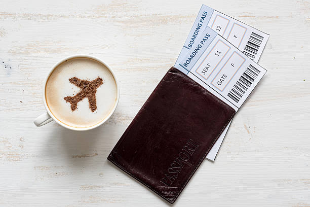 airplane made of cinnamon in cappuccino and boarding passes. - aeroplane ticket stock photos and pictures