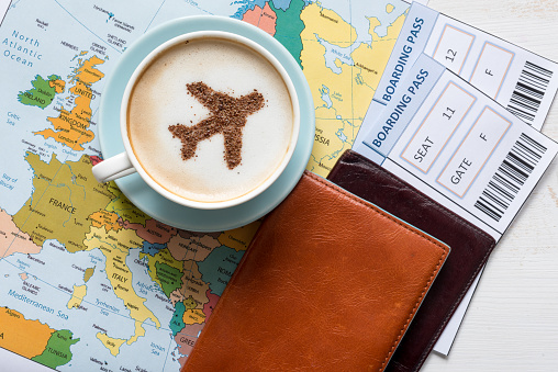 Airplane Made Of Cinnamon In Cappuccino Passports And Europe Map Stock Photo - Download Image Now