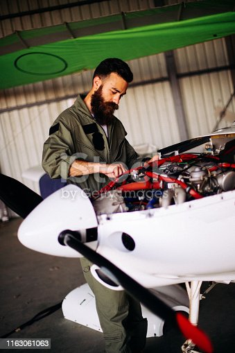 A young bearded man repairing the engine of a sports plane in a hangar.