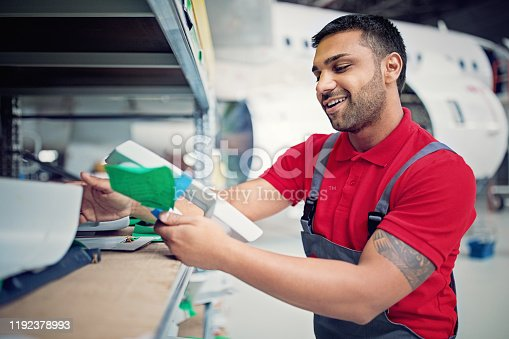1047558948 istock photo Airplane mechanic is choosing parts for planned aircraft maintenance in the hangar 1192378993