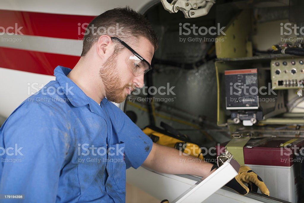 Airplane mechanic working on engine of private jet royalty-free stock photo