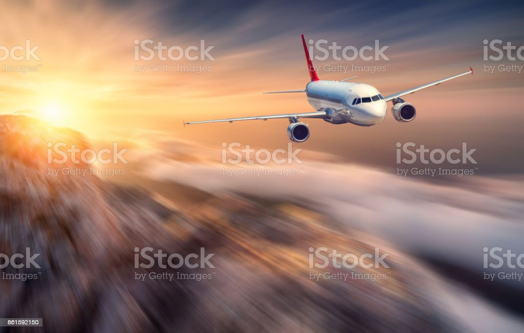 Airplane mith motion blur effect is flying over low clouds at sunset. Landscape with passenger airplane, blurred clouds, mountains, sun. Passenger aircraft. Business travel. Commercial plane. Concept stock photo