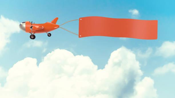 flugzeug modell orange farbe mit leeren banner mock-up - bandanzeige stock-fotos und bilder