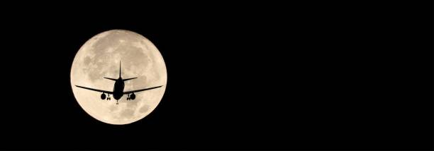 Airplane on a full moon background stock photo