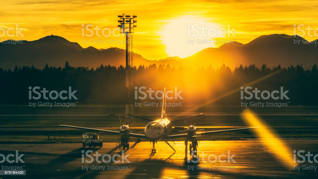 Airplane on airport runway at sunset stock photo