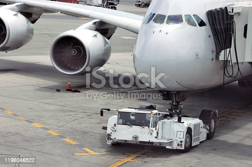 airplane on airport runway with pushback tractor attached to plane nose gear