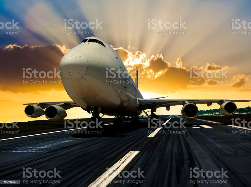 Airplane on runway  at the sunrise stock photo