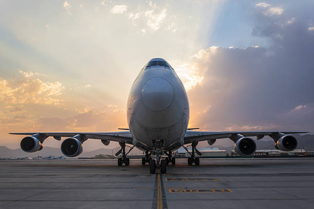Airplane on taxiway at sunset stock photo