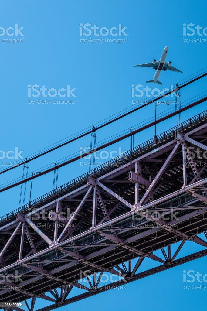 Airplane over 25 April bridge in Lisbon - Zbiór zdjęć royalty-free (Fotografika)