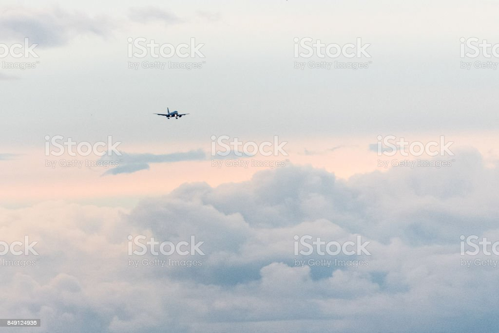Airplane over clouds on final approach for landing. stock photo