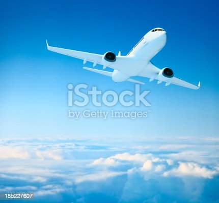 istock Airplane over clouds 185227607