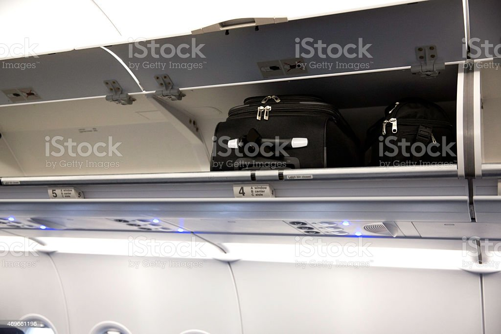 Airplane overhead carry-on luggage compartments stock photo