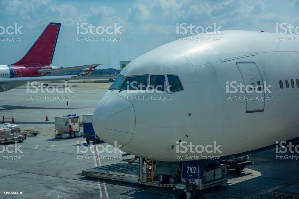 Flygplan som parkerade på flygplatsterminalen med aerobridge ansluten - Royaltyfri Ankomst Bildbanksbilder