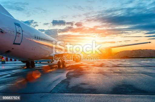 istock Airplane parked at the airport at dawn in the sky clouds sun 936837524