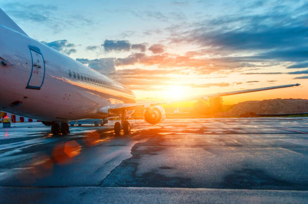 Airplane parked at the airport at dawn in the sky clouds sun stock photo