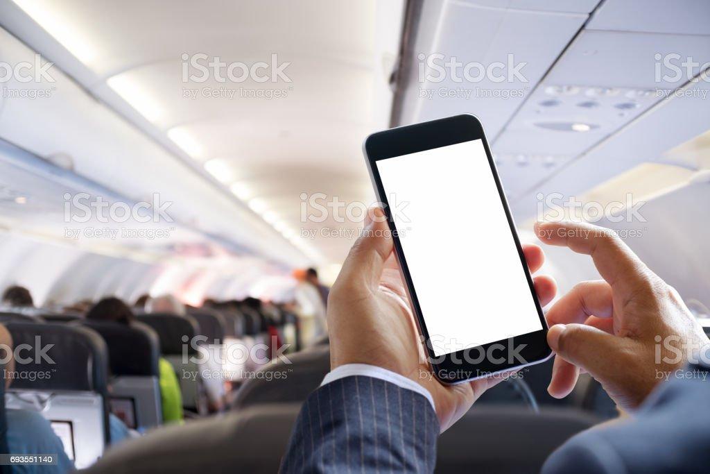 Airplane passenger using smart phone on plane. stock photo