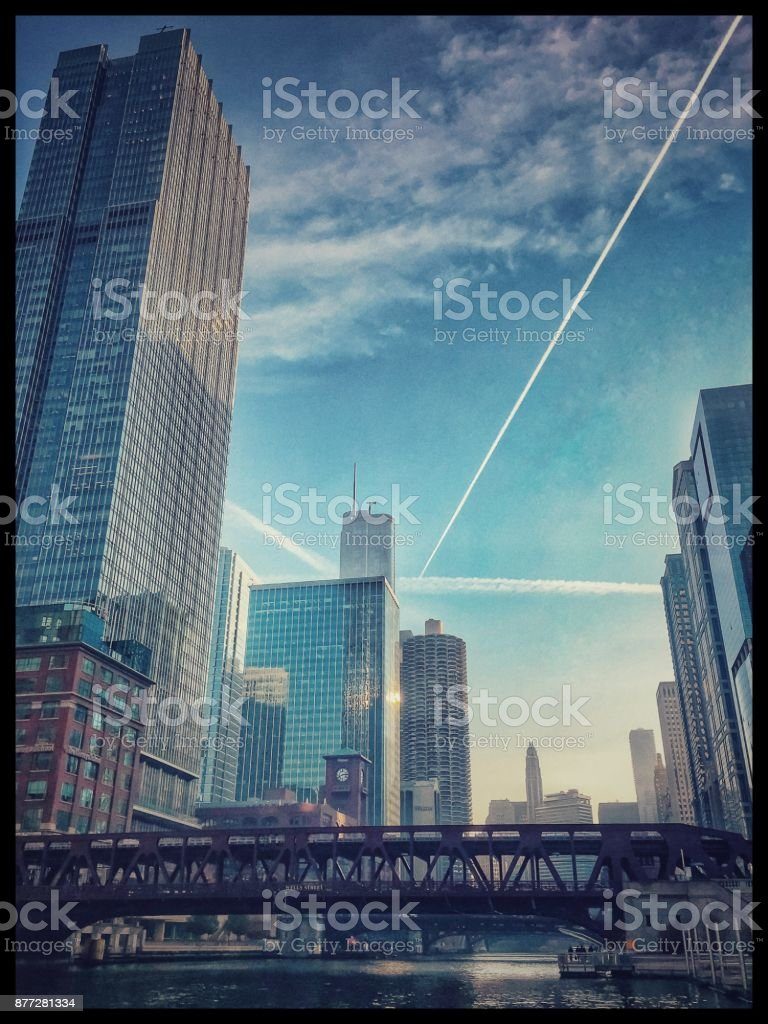 Airplane patterns in sky over Chicago River during morning commute stock photo