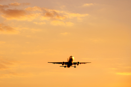 commercial airplane taking off during sunset.
