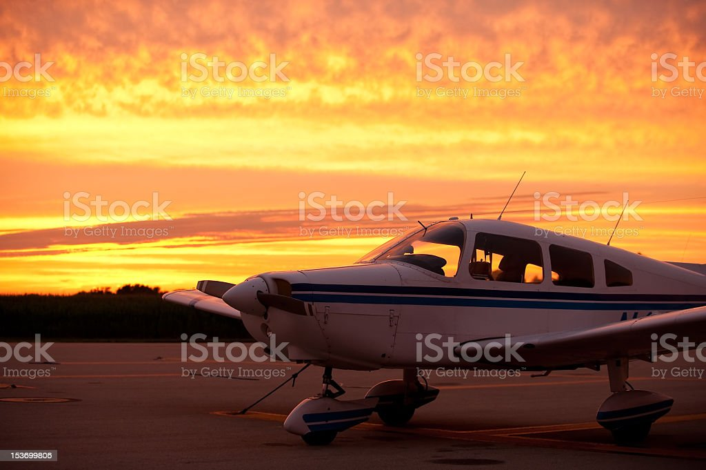Airplane ready to fly at sunset stock photo
