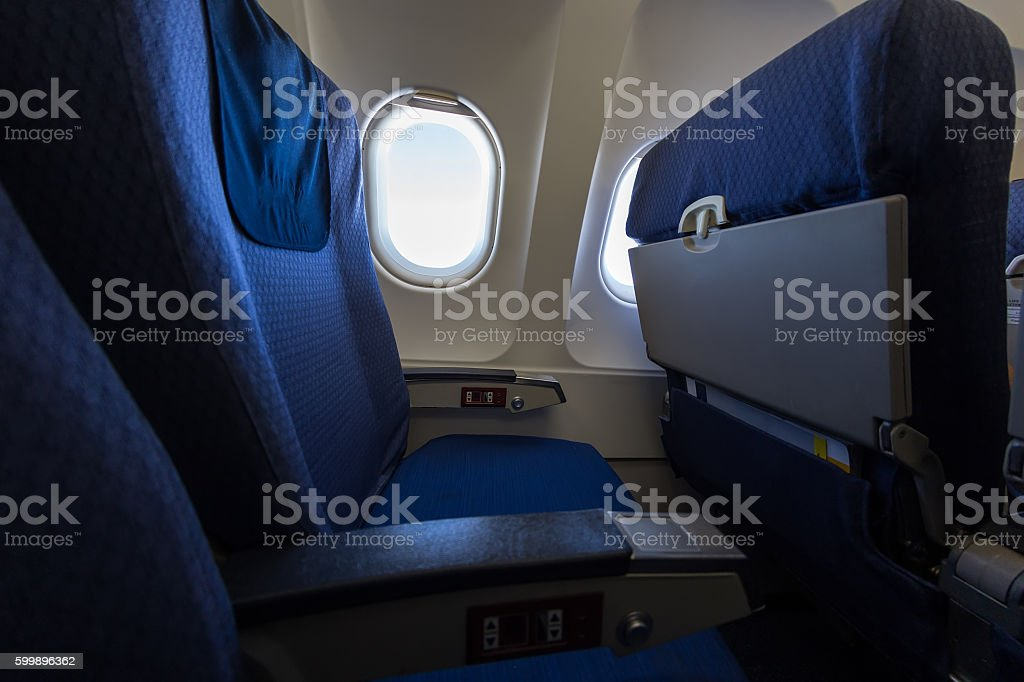 Airplane seat and window inside an aircraft. stock photo