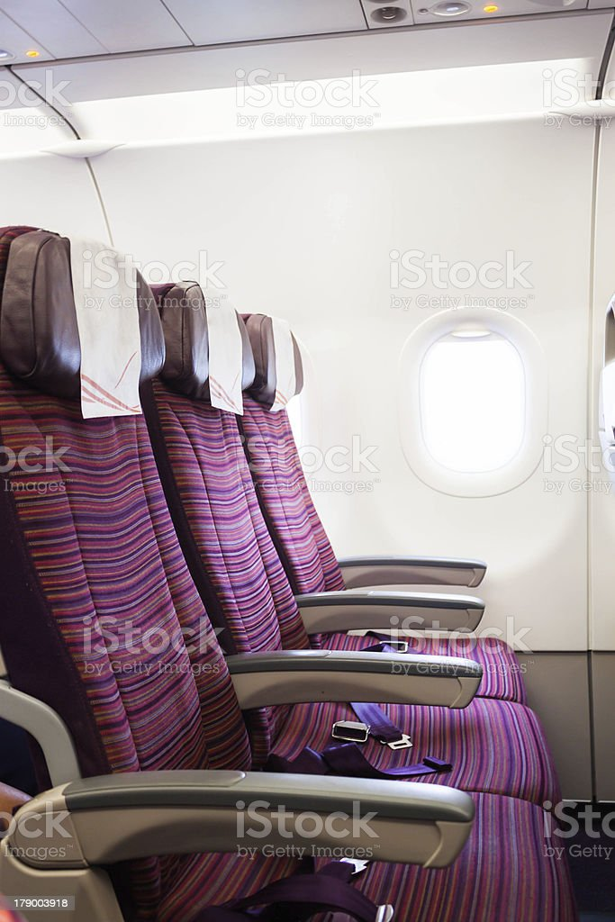 Airplane seat row in passenger cabin with window beside stock photo