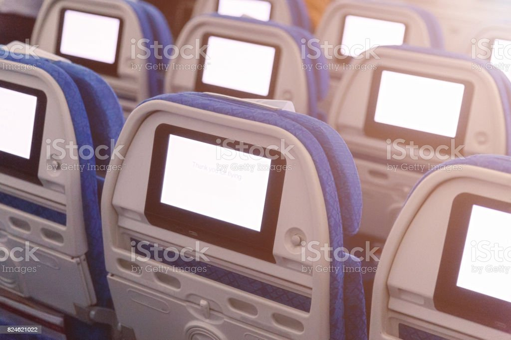 Airplane seat with screens in chairs back stock photo