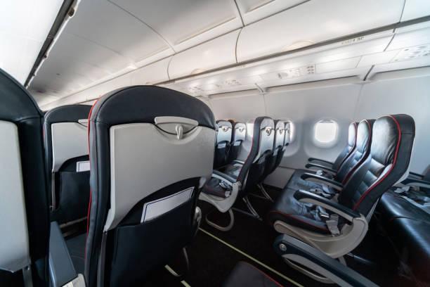 flugzeugsitze und fenster. economy class bequeme sitze ohne passagiere. neue billigfluggesellschaft - billigflüge buchen stock-fotos und bilder