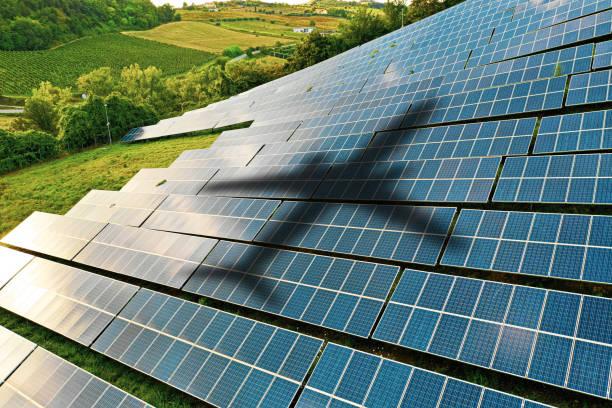 Airplane shape against solar panels stock photo